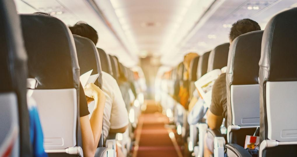 Airline aisle with people sitting in the seats