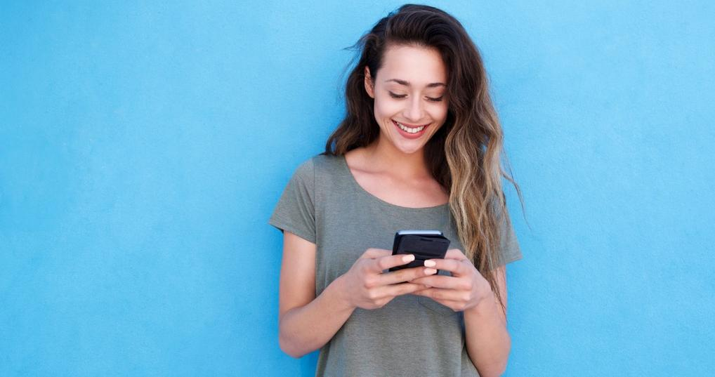 Young smiling woman using her phone