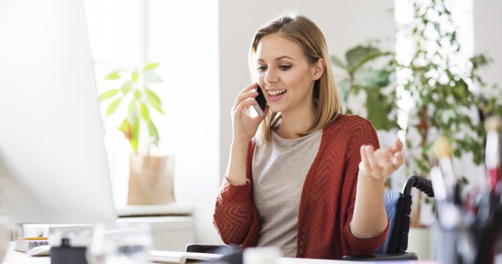 Business woman talking on her cell phone at her desk