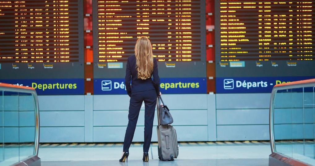 Business woman at international airport reviewing her gate number