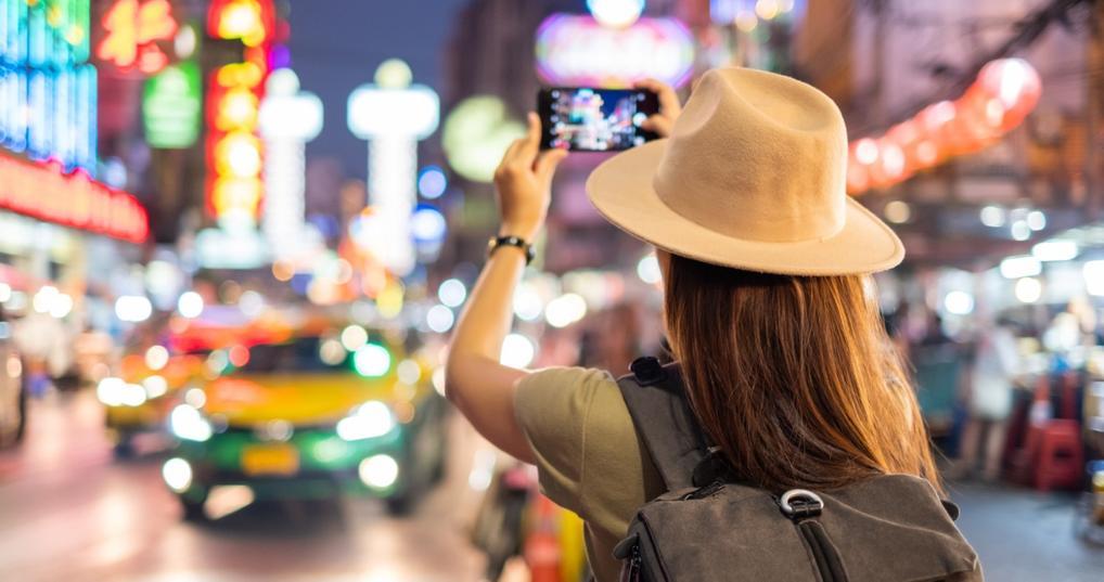 Tourist woman taking a photo of a night time market