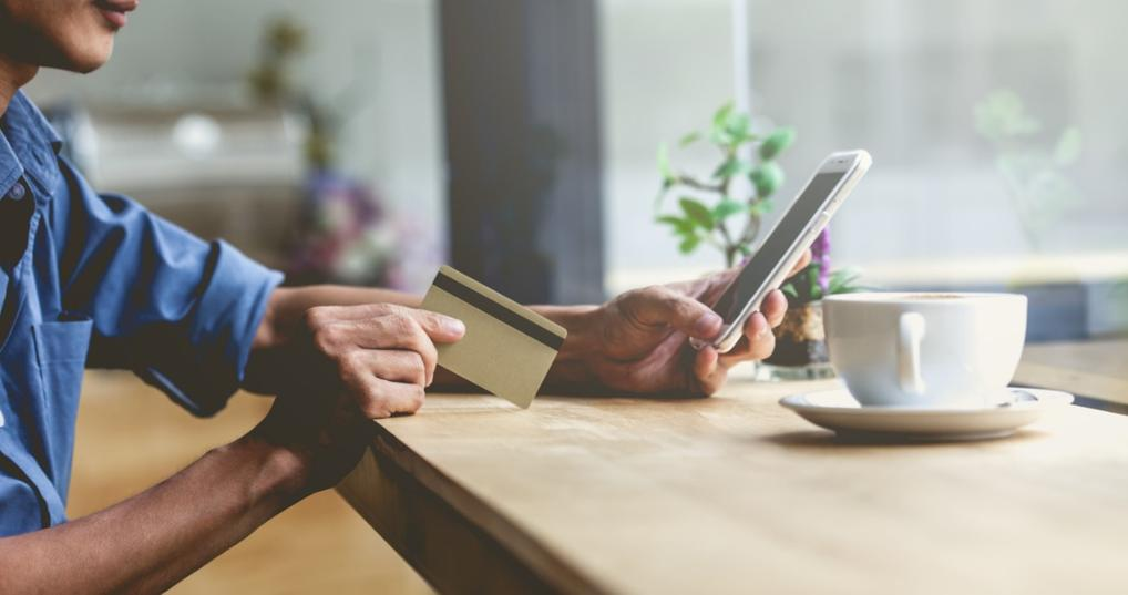 Man holding a credit card and using smartphone