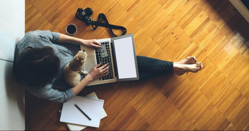 Woman sitting on the floor with her dog holding a credit card and laptop