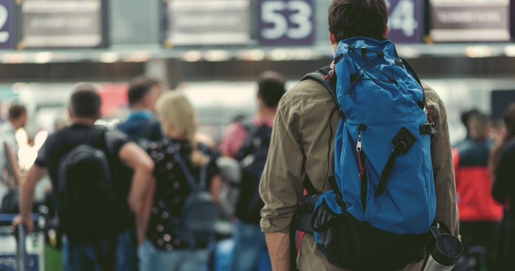 Man with blue backpack waiting at airport