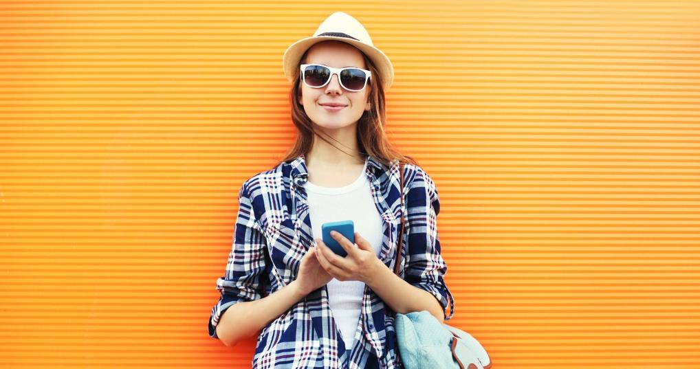 woman holding phone checking money app