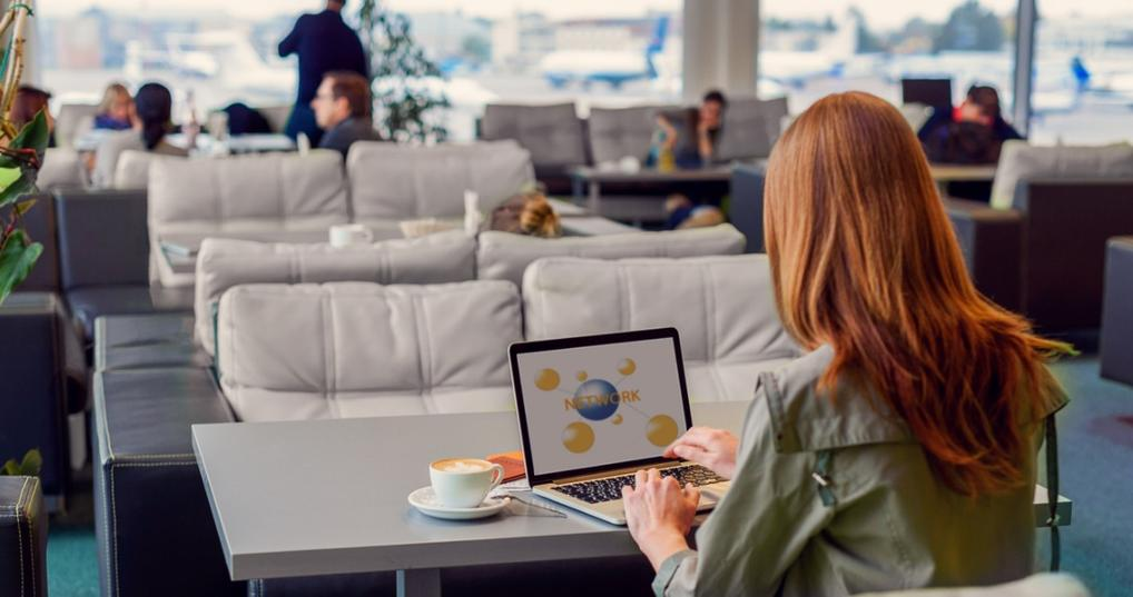 Woman working on a laptop in an airport lounge