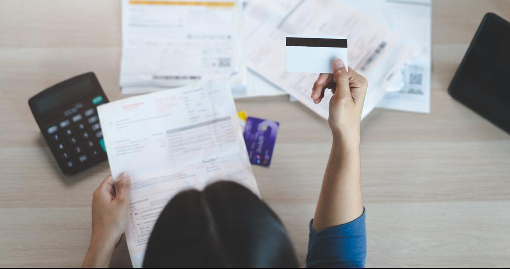 Young woman looking at her credit cards and bills