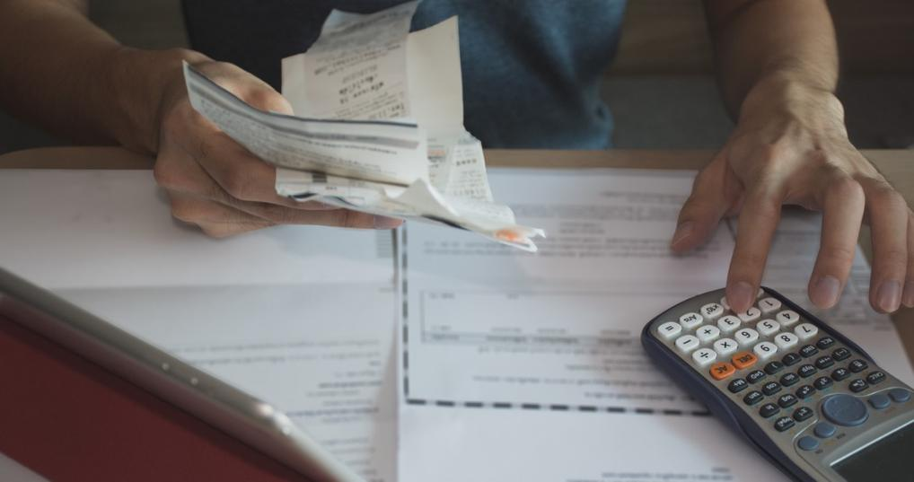 Man calculating his bills for a debt management plan