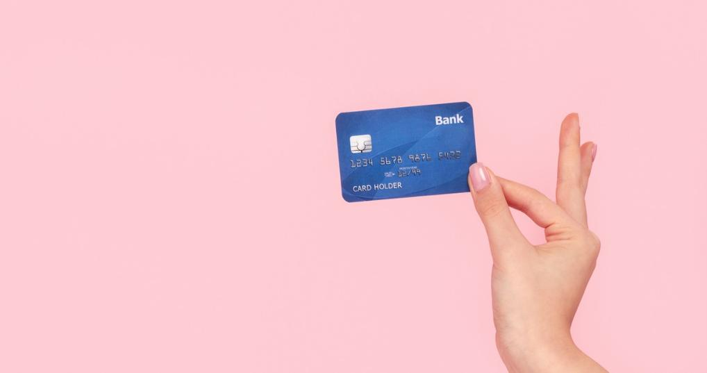 A woman's hand holding a blue credit card