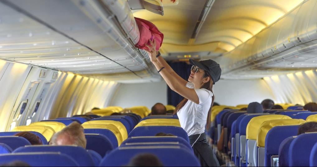 Woman putting her bag in the overhead compartment on an airplane