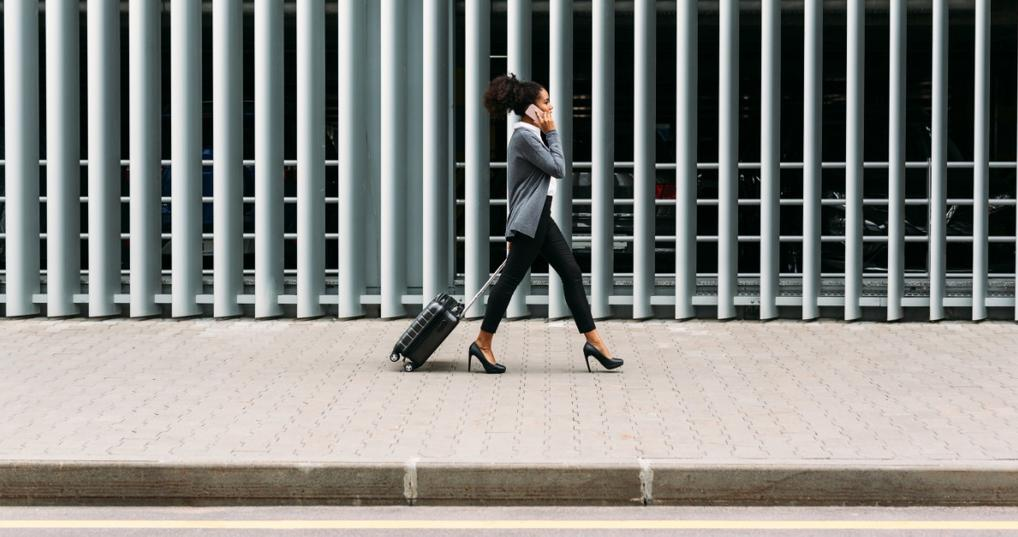 Business woman walking with a suitcase