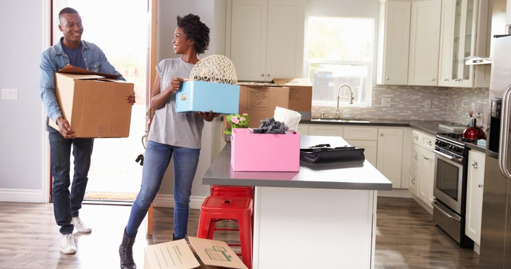 Young couple moving boxes into a new house