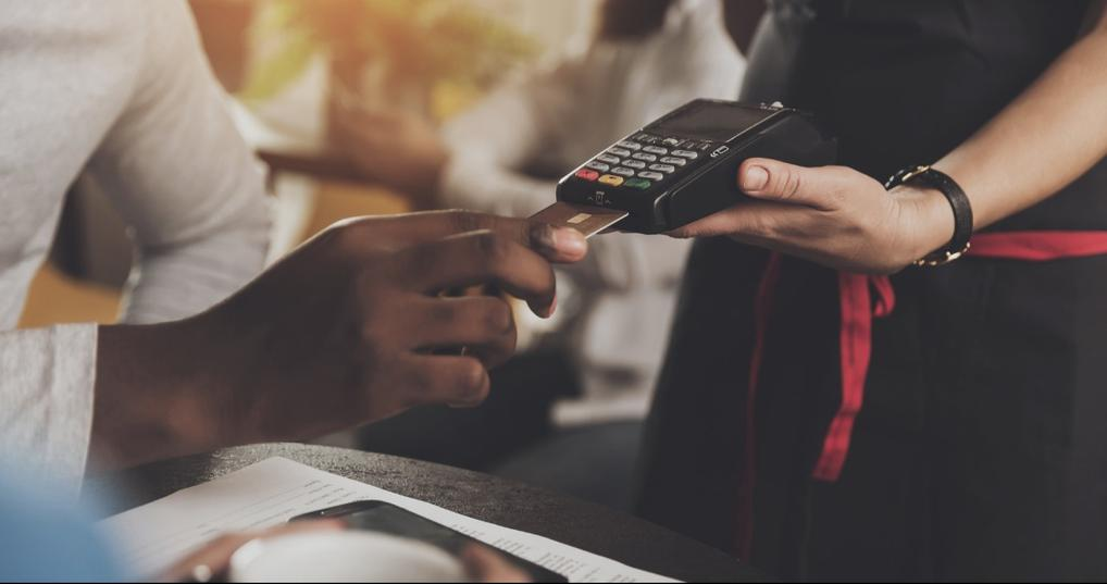 Man at a restaurant paying with a secured credit card