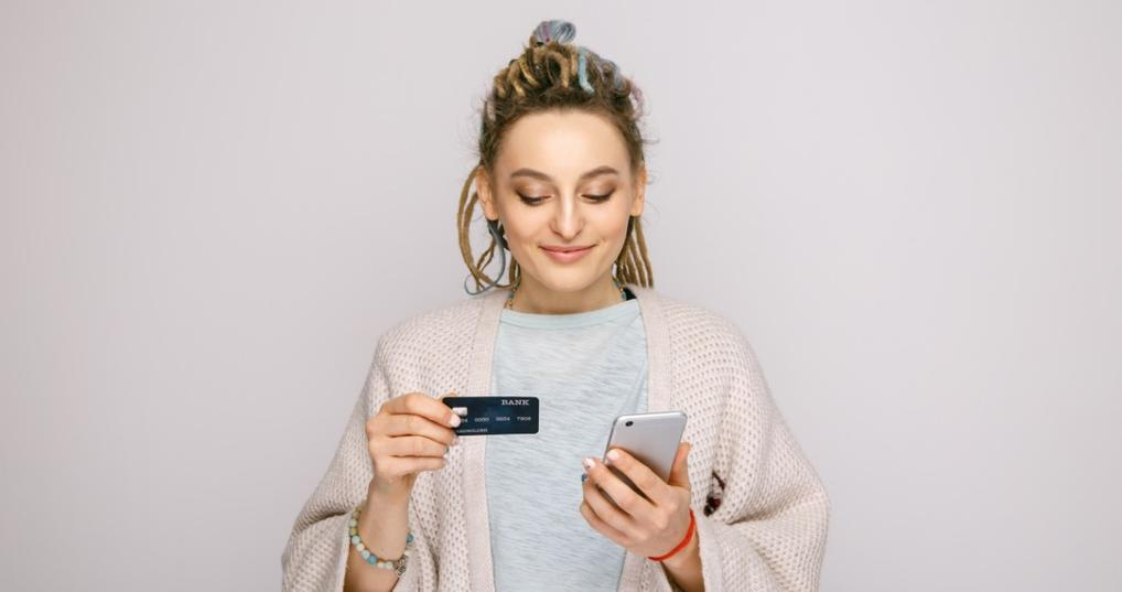 Girl looking at her credit card and phone