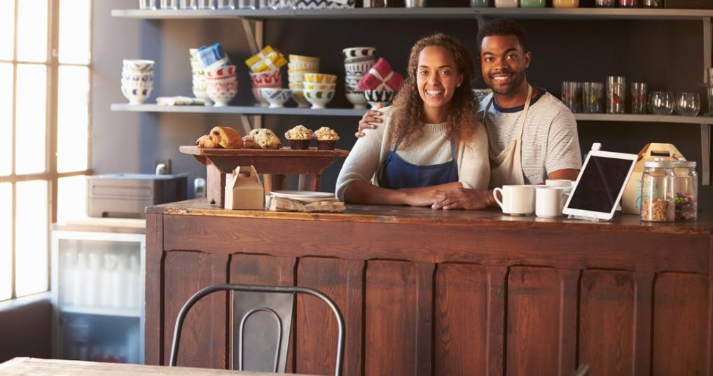 Cafe owners smiling behind the counter