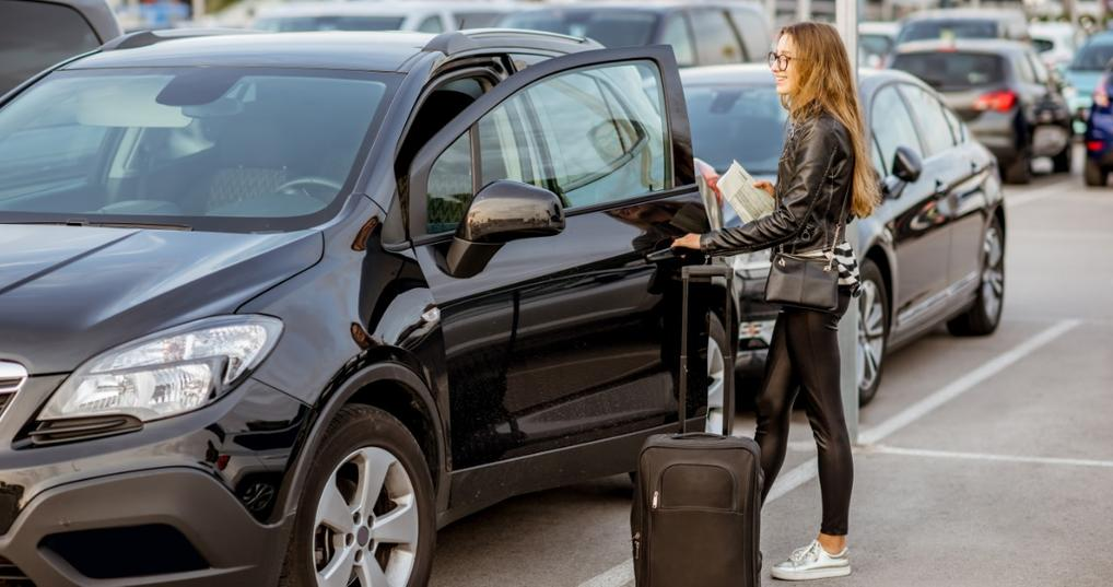Woman picking up her rental car in a parking lot