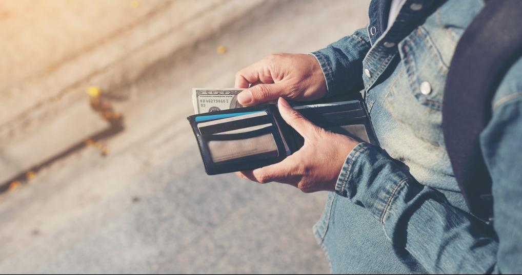 Man pulling cash out of his wallet to pay fees