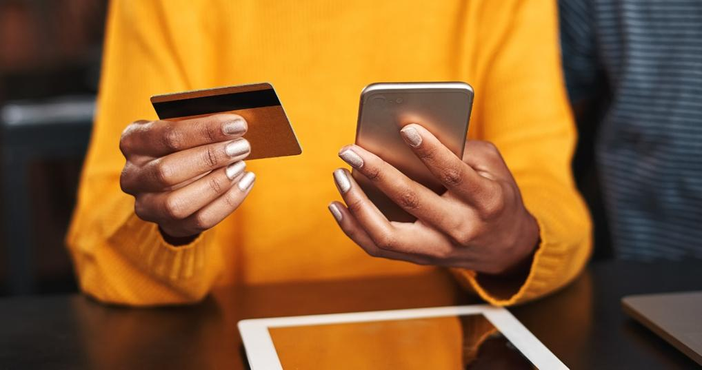 Woman research cash back vs. miles credit cards