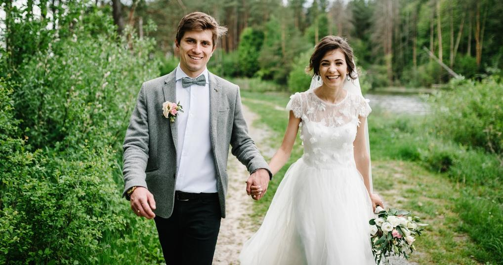 A bride and groom holding hands outside