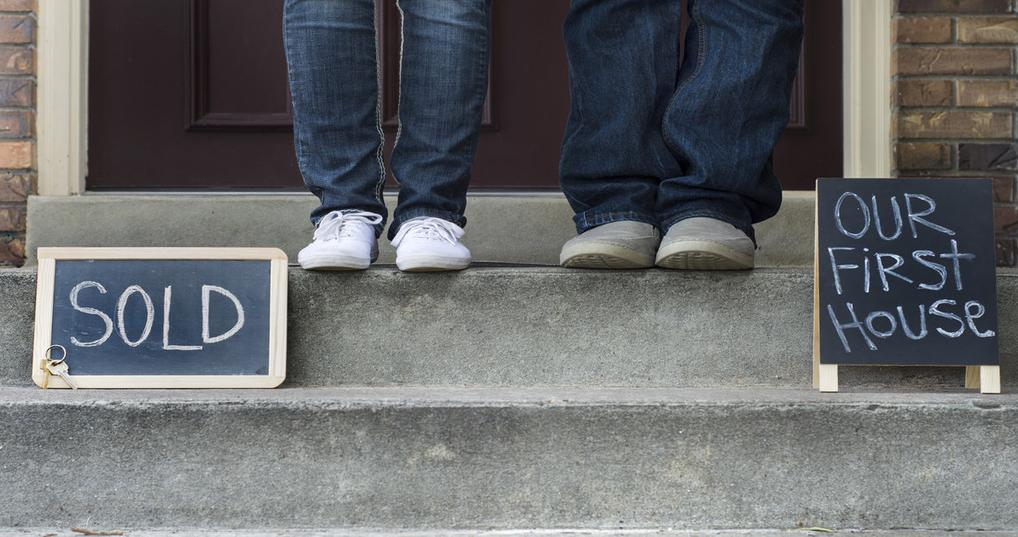 couple standing on stairs of new home