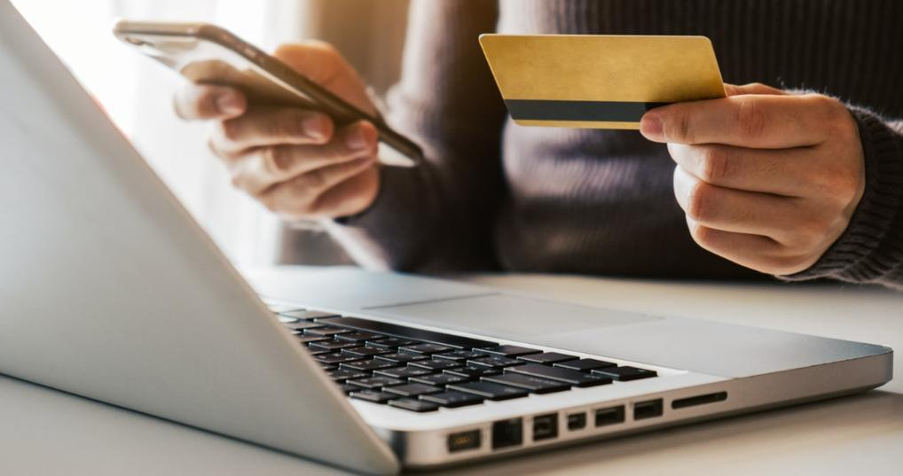 Man with smartphone looking at credit card