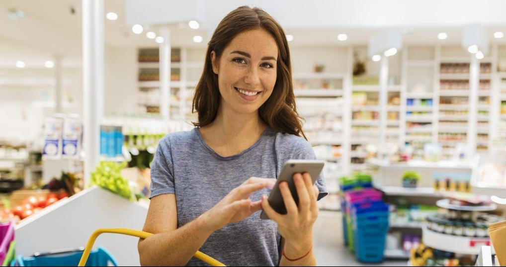 Woman smiling at phone while shopping