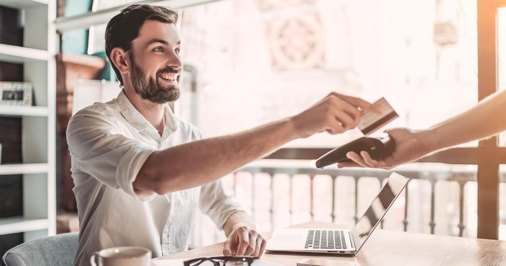 Smiling man using credit card
