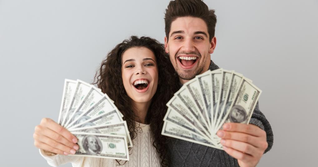 Enthusiastic couple holding money