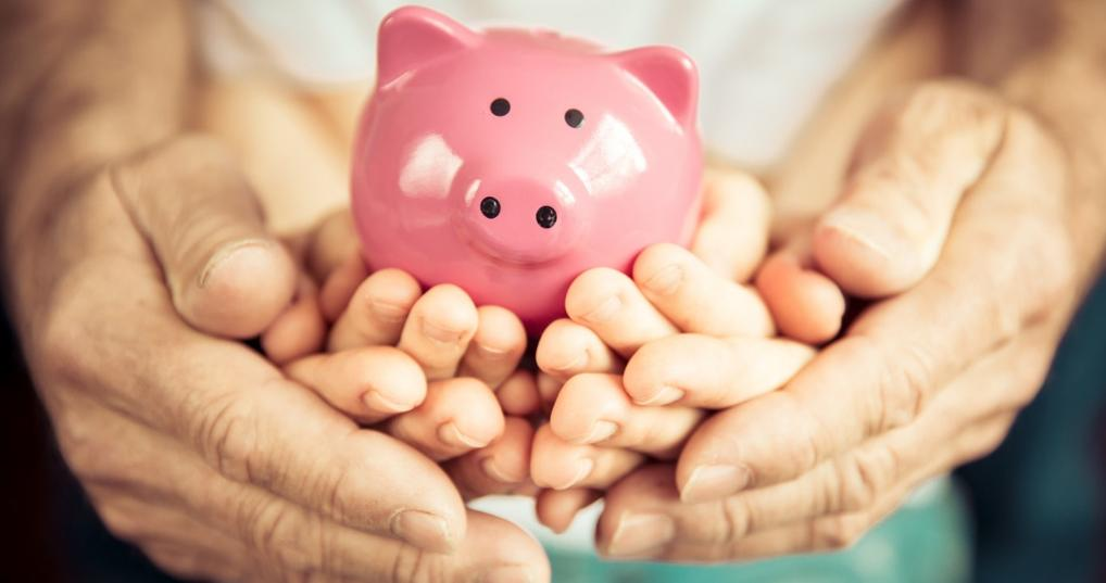 Parent and child holding piggy bank