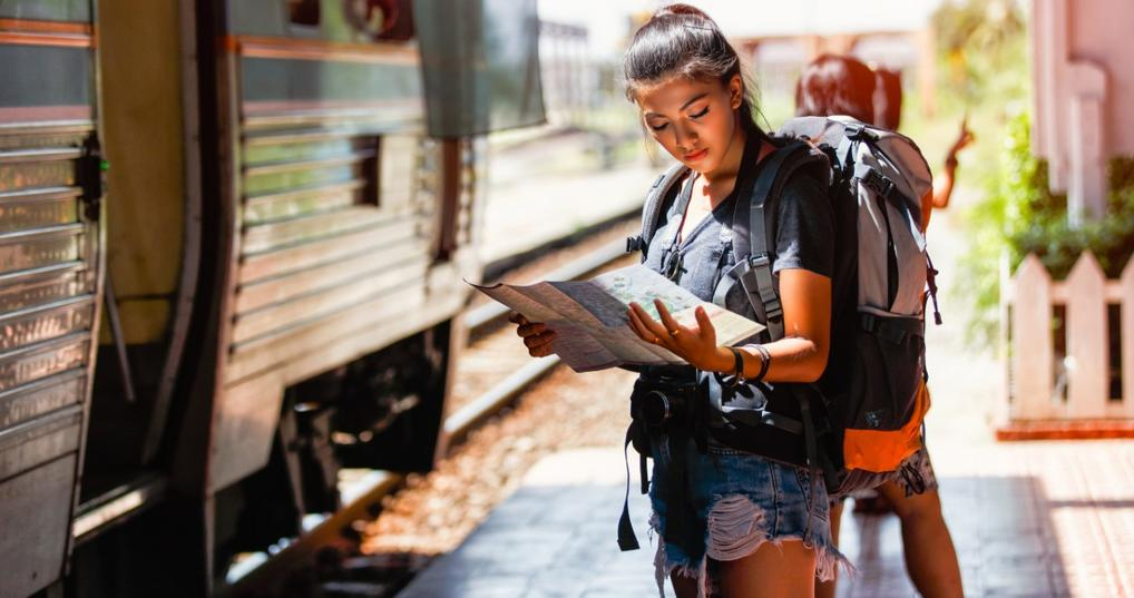 Woman with travel backpack looking at a map
