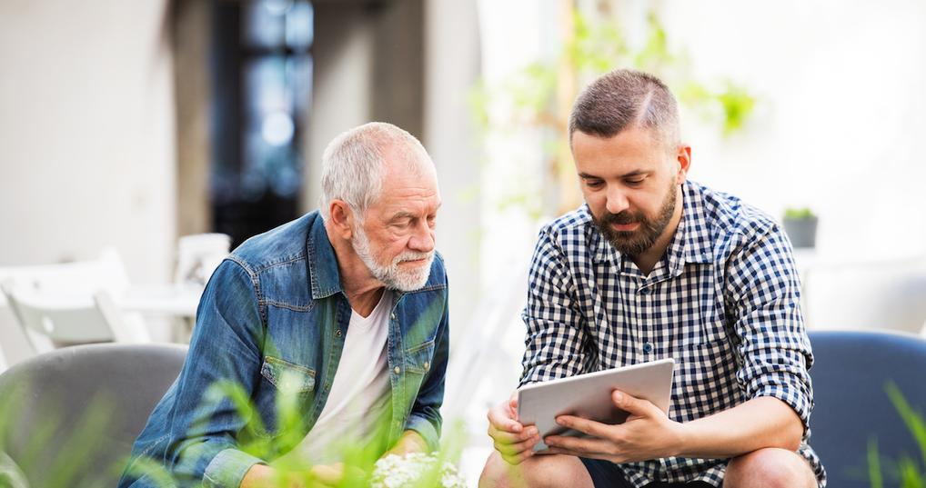 Elderly man talking with adult son