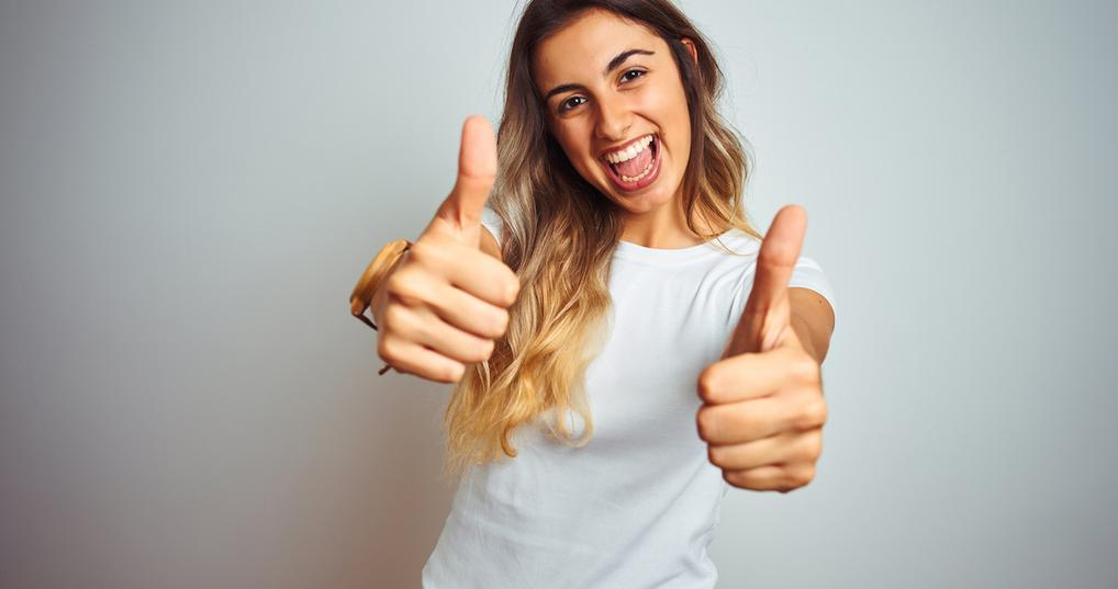 Enthusiastic woman giving two thumbs up