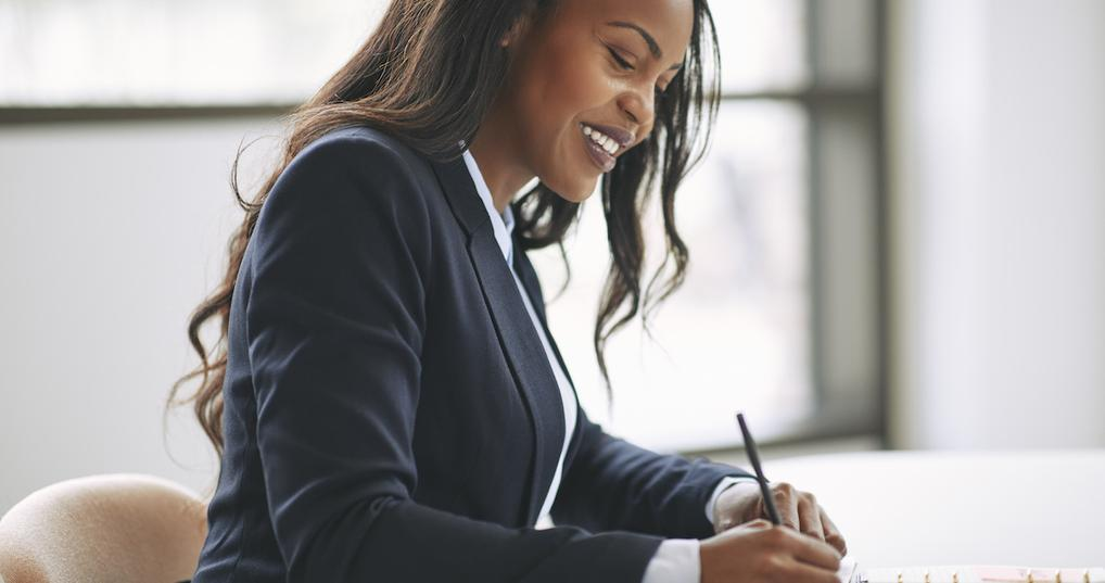 Smiling businesswoman writing