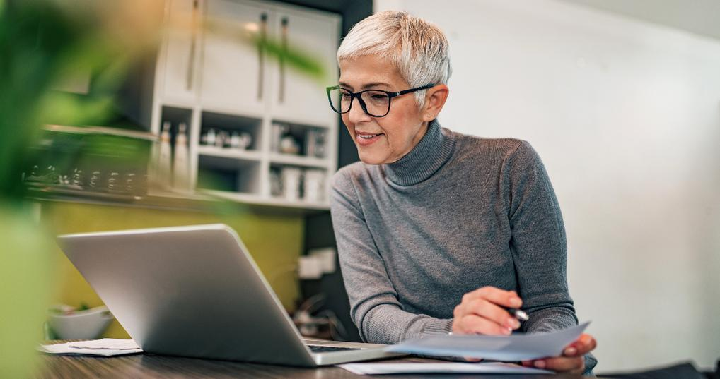 retired woman working at laptop on side hustle