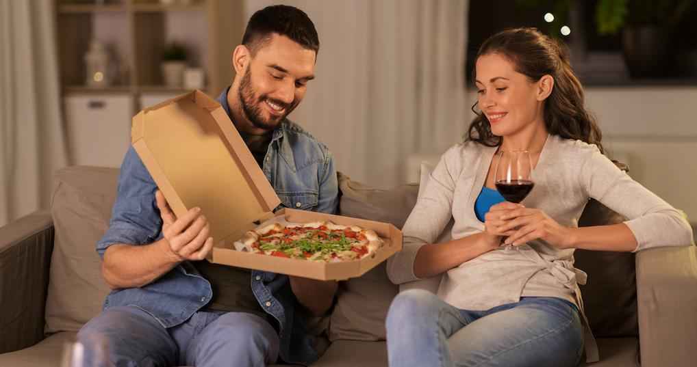 Couple enjoying pizza and wine at home