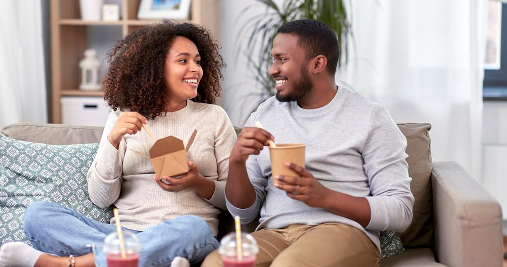 Happy couple eating takeout at home