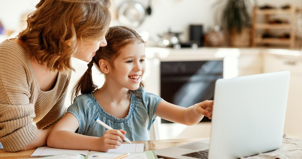 Happy girl using laptop with mother