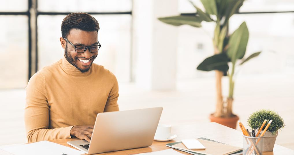 Smiling man using laptop