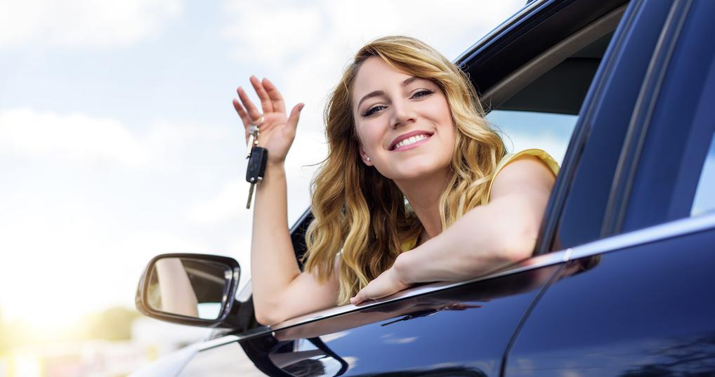 Smiling woman holding car key