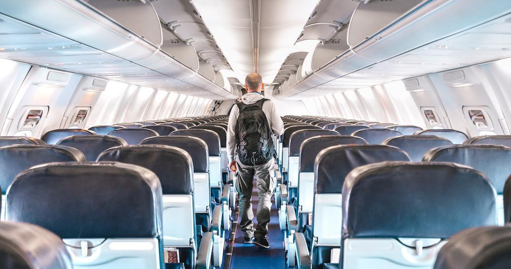 Man walking down airplane aisle