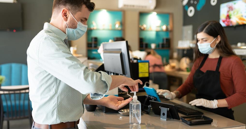 Man using hand sanitizer at restaurant