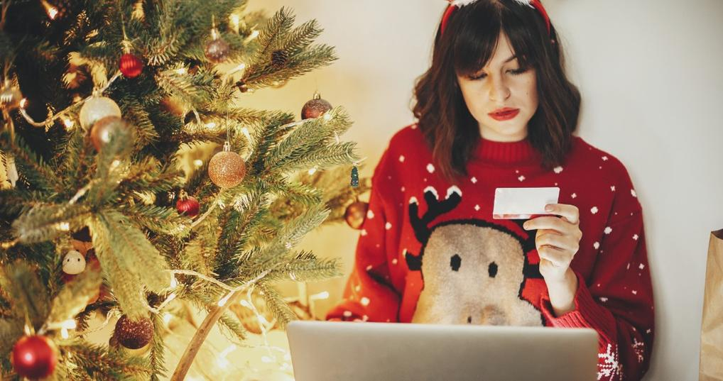 woman in holiday sweater shopping online