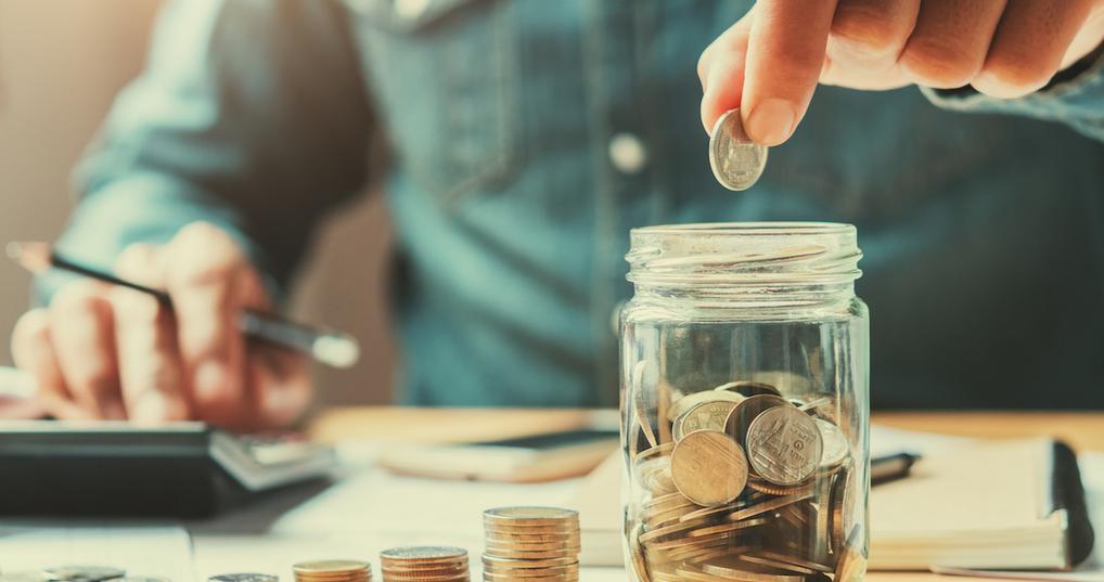 Man adding coins to jar
