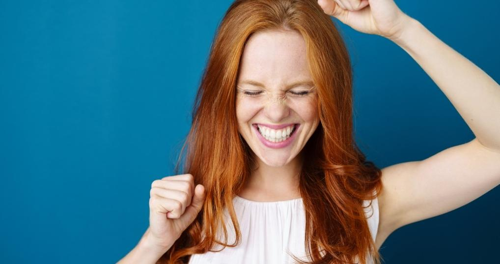 woman very happy and celebrating on blue background