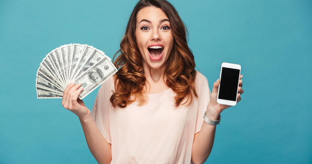 Excited woman holding money and smartphone