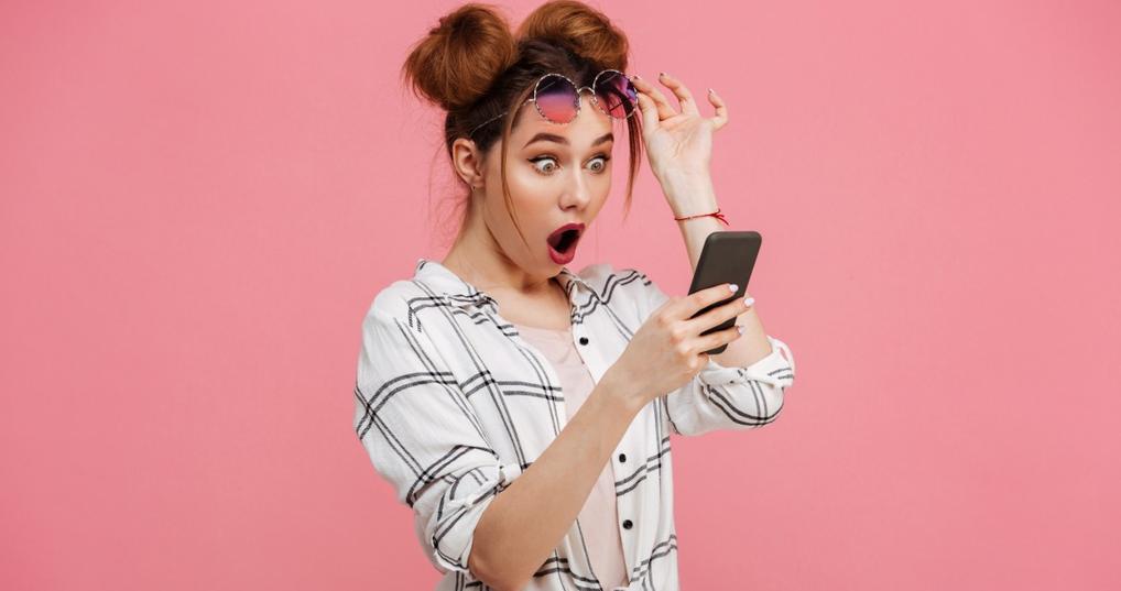 woman looking surprised at phone