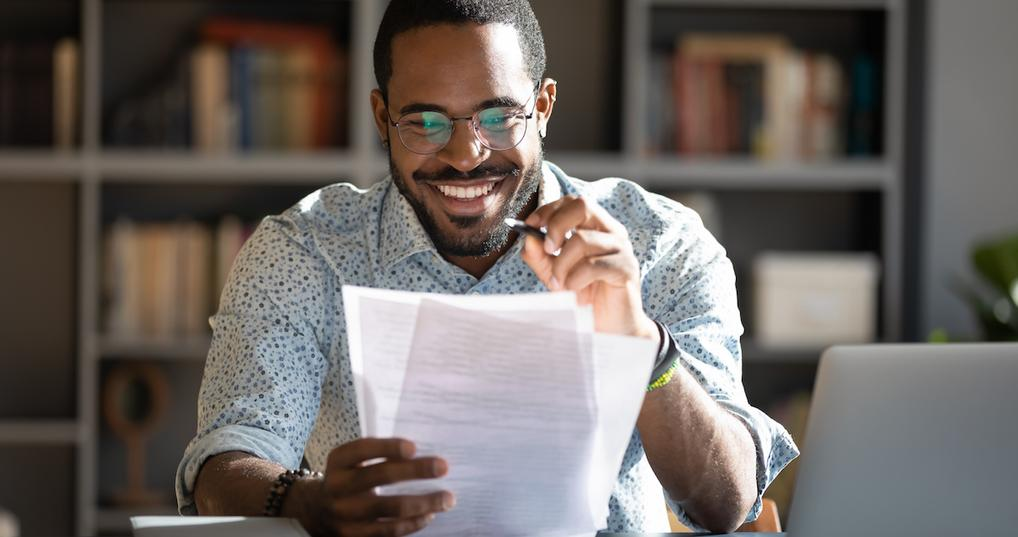 Smiling man looking at paperwork