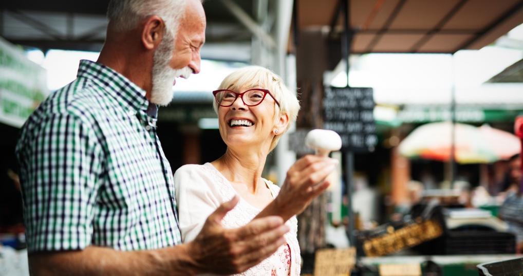 Portrait of beautiful elderly couple in market buying food