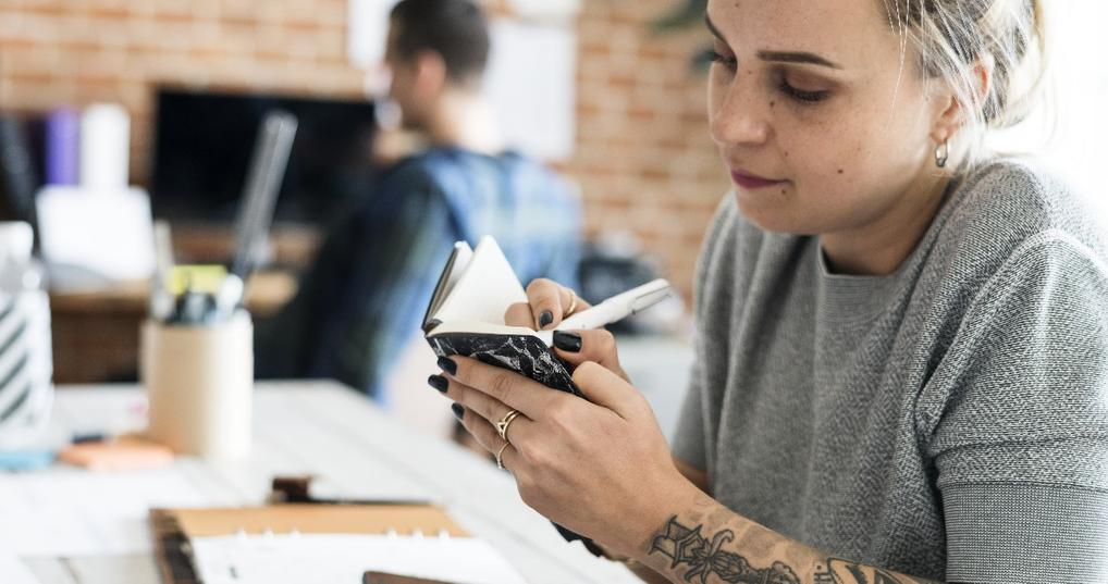 millennial woman with tattoos writing note