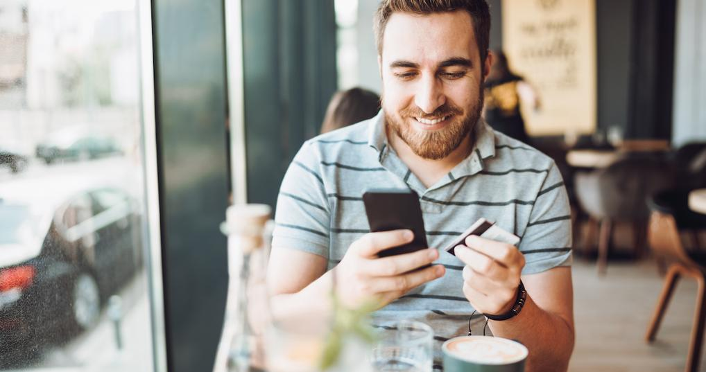 Man browsing Amex Offers in coffee shop